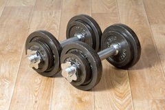 Dos pesas de gimnasia que se colocan en piso de madera Imagen de archivo