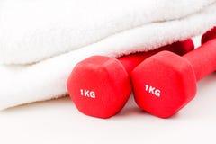 Dos pesas de gimnasia rojas y toalla blanca foto de archivo