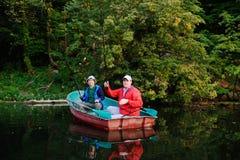Dos pescadores en un barco con las cañas de pescar que cogen pescados Imagen de archivo libre de regalías