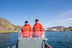 Dos pescadores navegan en un barco de motor en el mar a lo largo del horizonte Imagen de archivo