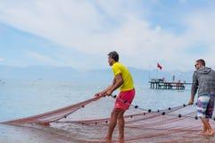Dos pescadores que preparan la red de pesca para comenzar día laboral en la costa del océano, mar Forma de vida sana emociones hu Imagenes de archivo