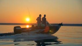 Dos pescadores se están moviendo a través de waterscape de la salida del sol en una lancha de carreras almacen de metraje de vídeo