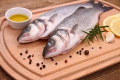 Dos pescados frescos de la lubina en tabla de cortar con los ingredientes imagen de archivo libre de regalías
