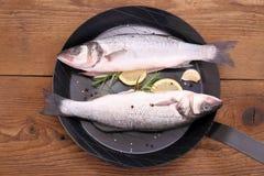 Dos pescados frescos de los moronidae en el sartén con el ingrediente imagenes de archivo