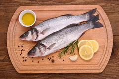 Dos pescados frescos de los moronidae en tabla de cortar con los ingredientes Fotografía de archivo libre de regalías