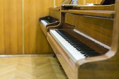 Dos pianos marrones en la clase de música Ciérrese para arriba de llaves del piano en la sala de clase foto de archivo