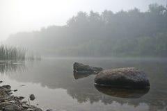 Dos piedras en el río en la costa en niebla fotos de archivo
