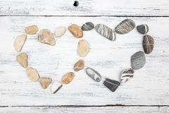 Dos piedras en forma de corazón del guijarro en una madera vieja Foto de archivo