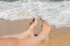 Dos piernas mienten en una playa del mar en un fondo de la onda Foto de archivo
