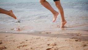 Dos piernas que corren en la playa, cámara lenta de los niños