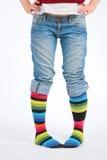 Dos pies en calcetines multicolores Imágenes de archivo libres de regalías