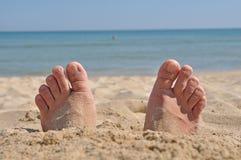 Dos pies enterrados en arena Imagen de archivo