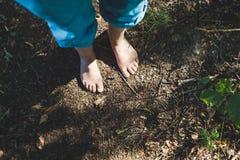 Dos pies femeninos se están colocando en el piso del bosque imagen de archivo