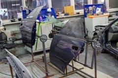 Dos piezas azules de la puerta del coche están instaladas en los estantes después de paintin foto de archivo