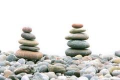 Dos pilas de piedras sobre blanco Imágenes de archivo libres de regalías