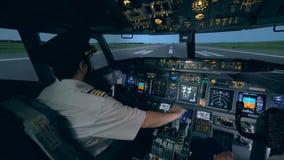 Dos pilotos están en una carlinga, mientras que un avión va en una pista 4K almacen de metraje de vídeo