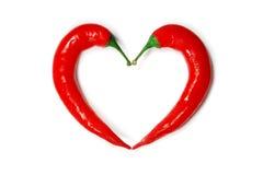 Dos pimientas de chile que forman una dimensión de una variable del corazón imagen de archivo