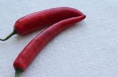 Dos pimientas de chiles frescas rojas en fondo de la arpillera Foto de archivo libre de regalías
