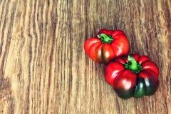 Dos pimientas rojas dulces en fondo de madera rústico Imagen entonada Fotografía de archivo libre de regalías