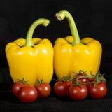 Dos pimientas se preparan para entrar en la cocina Fotos de archivo
