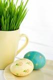 Dos pintaron los huevos de Pascua con una taza de hierba verde fotos de archivo libres de regalías