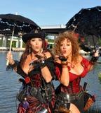 Dos piratas de sexo femenino hermosos con los parasoles soplan un beso Foto de archivo