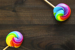 Dos piruletas coloreadas arco iris en fondo de madera azul Foto de archivo libre de regalías