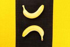 Dos plátanos maduros amarillos de las zonas tropicales en un napki del bambú negro Imagen de archivo libre de regalías