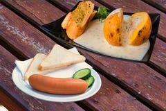 Dos placas con los alimentos de preparación rápida en una tabla de madera Foto de archivo