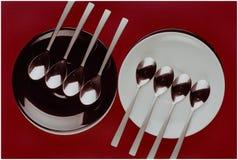 Dos placas y ocho cucharas Imagenes de archivo