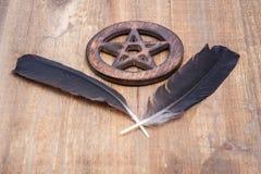 Dos plumas negras del cuervo y símbolo cercado de madera del Pentagram en la madera Cinco elementos: Tierra, agua, aire, fuego, a imagen de archivo