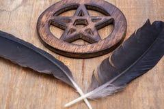 Dos plumas negras del cuervo y símbolo cercado de madera del Pentagram en la madera Cinco elementos: Tierra, agua, aire, fuego, a foto de archivo libre de regalías