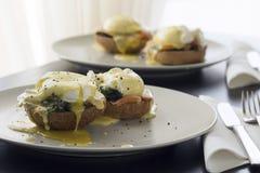 Dos porciones de los huevos Benedicto con los salmones y la espinaca Foto de archivo