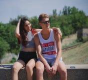 Dos positivos, adolescencias frescas que se sientan en un fondo natural Pares románticos lindos en un parque de la ciudad Concept Imagen de archivo libre de regalías