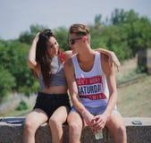 Dos positivos, adolescencias frescas que se sientan en un fondo natural Pares románticos lindos en un parque de la ciudad Concept Foto de archivo libre de regalías