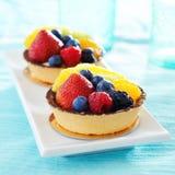 Dos postres aux. de las frutas del tarte en una placa fotos de archivo