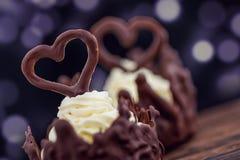Dos postres del chocolate llenaron de la crema blanca el la tabla de madera, el postre con los corazones del chocolate para las t Foto de archivo