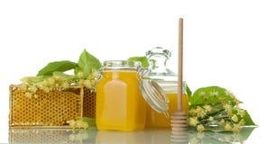 Dos potes con la miel, la cuchara de madera y el panal aislados en blanco Imagen de archivo