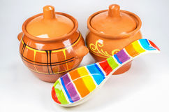 Dos potes de arcilla marrones con la cuchara de cerámica coloreada en el fondo blanco Fotografía de archivo libre de regalías