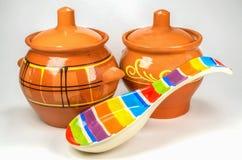 Dos potes de arcilla marrones con la cuchara de cerámica coloreada en el fondo blanco Fotos de archivo libres de regalías