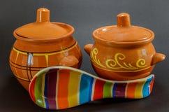 Dos potes de arcilla marrones con la cuchara de cerámica coloreada en fondo negro Fotos de archivo