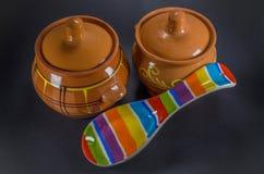 Dos potes de arcilla marrones con la cuchara de cerámica coloreada en fondo negro Fotos de archivo libres de regalías