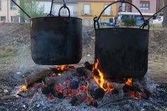 Dos potes de cobre grandes con los ollas de los firedes de madera de roble Fotografía de archivo libre de regalías
