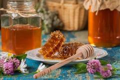 Dos potes de la miel con el panal en una tabla de madera Foto de archivo