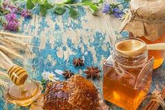 Dos potes de la miel con el panal en una tabla de madera con las flores Imágenes de archivo libres de regalías