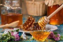 Dos potes de la miel con el panal en una tabla de madera con las flores Foto de archivo libre de regalías