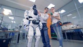 Dos profesionales están midiendo trabajando ajustes de un cyborg almacen de metraje de vídeo