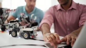 Dos profesionales jovenes que construyen el robot y que miran el ordenador portátil