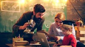 Dos profesores adultos traen al muchacho al proceso educativo Aprendizaje de concepto Alumnos en uniforme Profesor adentro metrajes