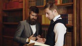 Dos profesores de sexo masculino que hablan o discutir la educaci?n en interior del vintage Concepto inteligente de la ?lite y de almacen de video